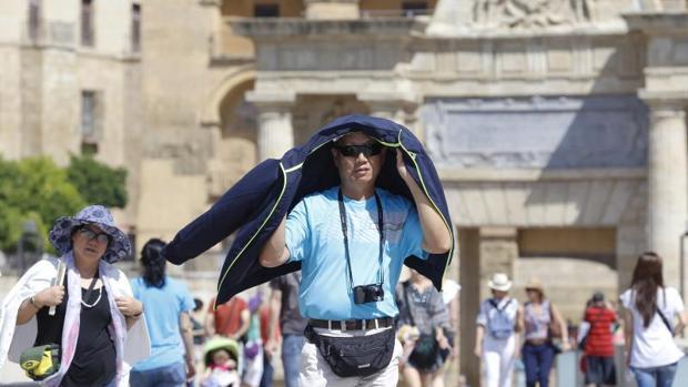 Un turista se protege del sol en el Puente Romano