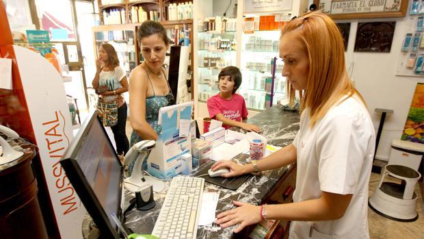 Una farmacéutica atiende a una cliente en una botica de Córdoba