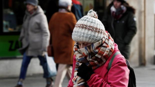 Una mujer se protege del frío con bufanda y gorro