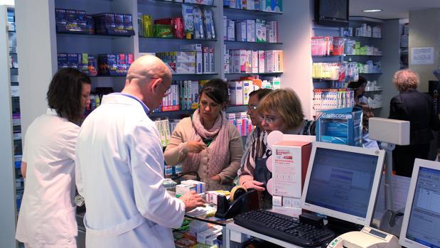 Farmacéuticos atienden a clientes en una farmacia