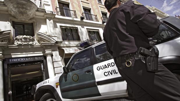 Un agente junto a un furgón de la Guardia Civil durante una redada en Sevilla