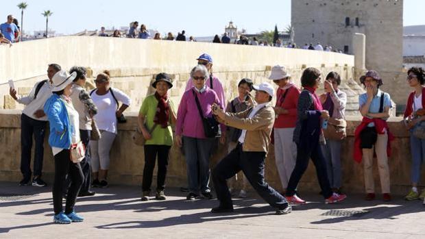 Un grupo de turistas se fotografían en el Puente Romano