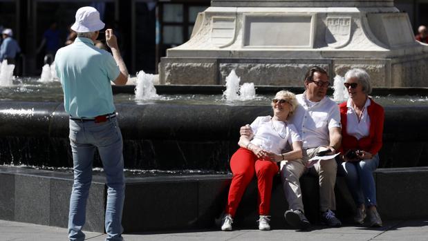 Turistas se fotografían en la fuente de Las Tendillas
