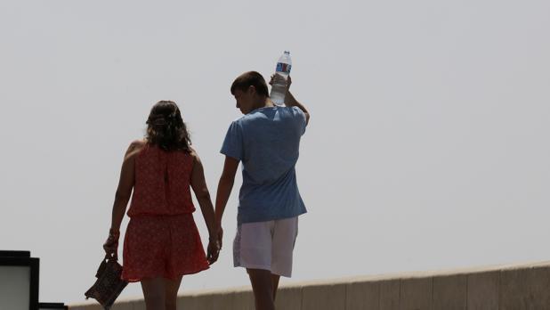 Una pareja pasea por el Puente Romano un día de calor
