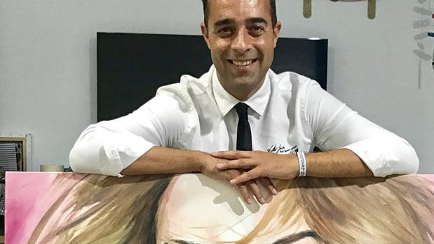 Alejandro Jeréz apoyado en el retrato de Jennifer López