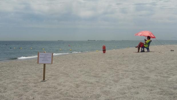 Imagen de la playa de El Burgo, con el cartel que prohíbe el baño