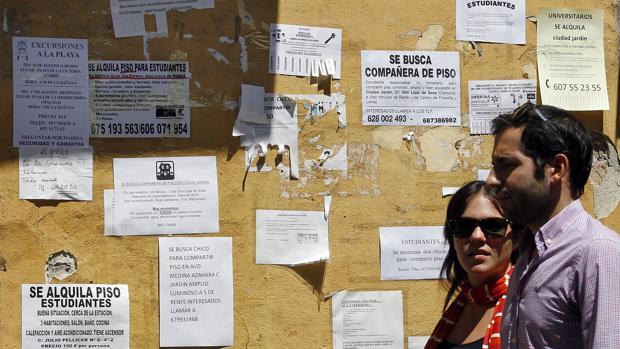 Una pareja pasa frente a una pared llena de anuncios de alquiler