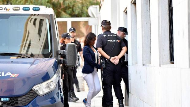 Ana Julia Quezada, custodiada por varios policías, entra en los juzgados