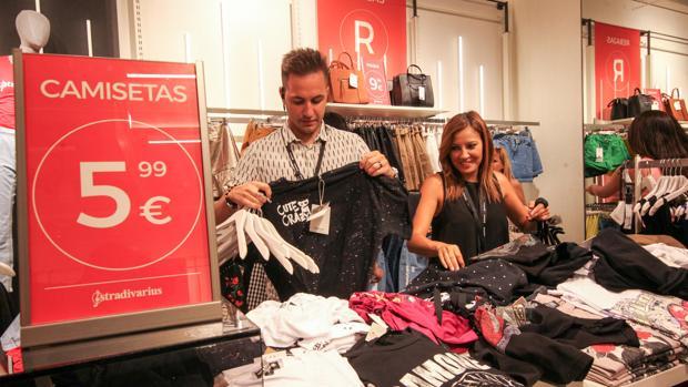 Jóvenes dependientes ordena la ropa en un comercio de la capital durante las rebajas en una imagen de archivo