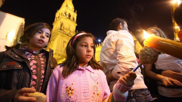 Dos niñas recogen cera en la Semana Santa de Córdoba