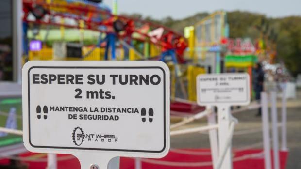 Montaje de atracciones de feria con carteles de las medidas de seguridad