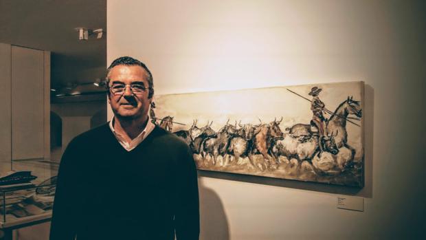 El ganadero y pintor Joaquín Lora junto a una de sus obras -