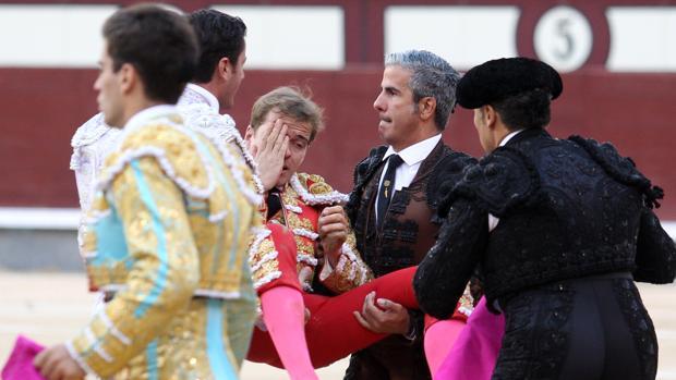 Javier Cortés se tapa el ojo dañado mientras es trasladado por las cuadrillas a la enfermería