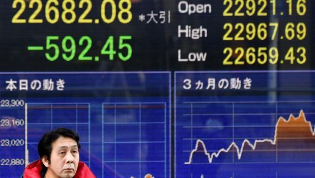 Un peatón pasa delante de una pantalla con los valores de la Bolsa de Tokio, en Japón