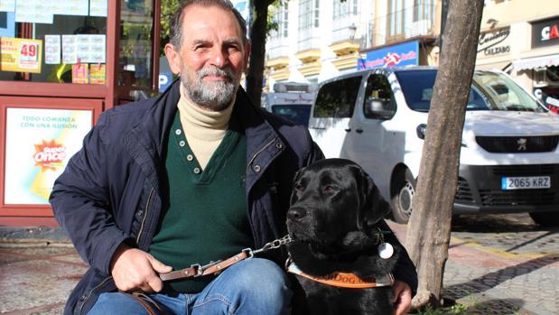 El utrerano Ricardo Fernández junto a su perro labrador que le sirve de guía