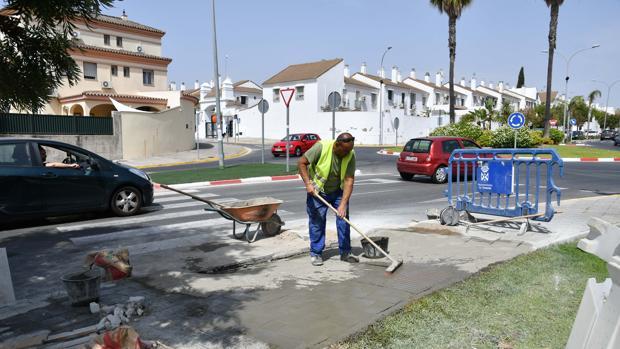Un operario trabaja sobre el paso de peatones de la Avenida del Aljarafe de Tomares