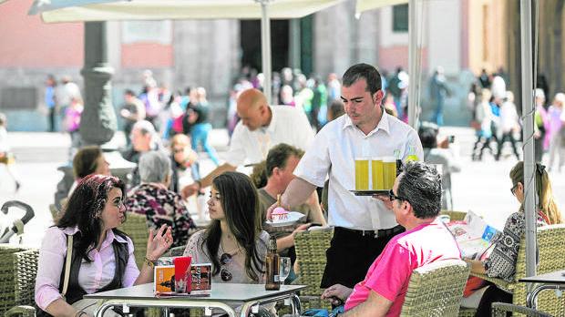 Un camarero atiende a los clientes en el centro de Sevilla