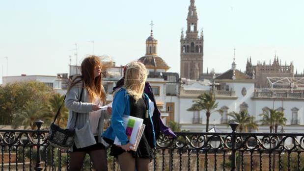Varias jóvenes cruzan el puente de Triana de Sevilla en una jornada con viento