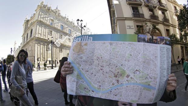 Dos turistas consultan un mapa de Sevilla en el Casco Histórico