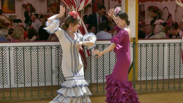 Dos jóvenes bailan sevillanas en el real de la Feria