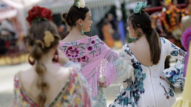 Unas jóvenes vestidas de flamenca pasean por el real