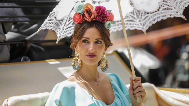 Una joven se cubre con una sombrilla en la Feria de Sevilla