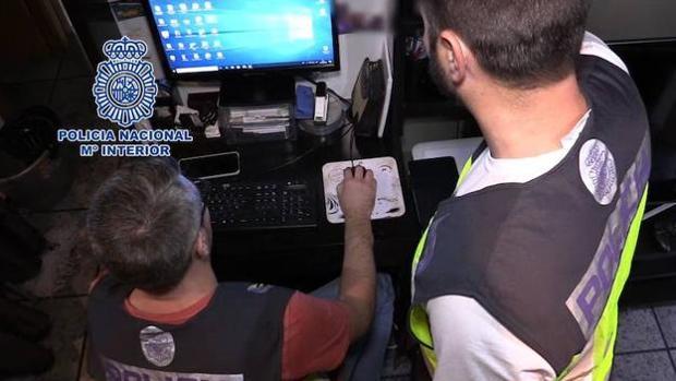 Imagen de archivo de dos agentes de Policía revisando el material intervenido en una operación
