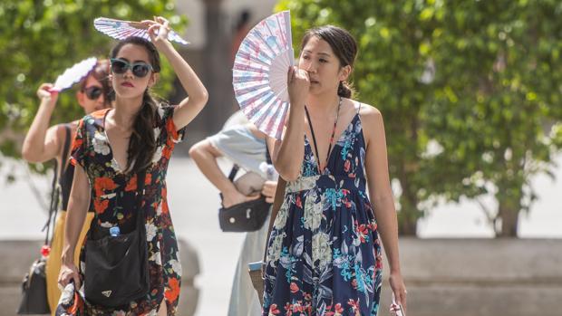 Dos turistas alivian el fuerte calor de Sevilla con unos abanicos