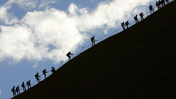 Turistas escalando el monolito de Uluru